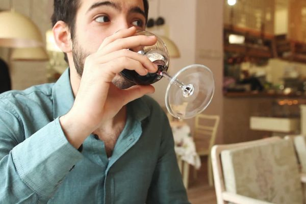handsome-young-man-drinking-wine-in-a-restaurant