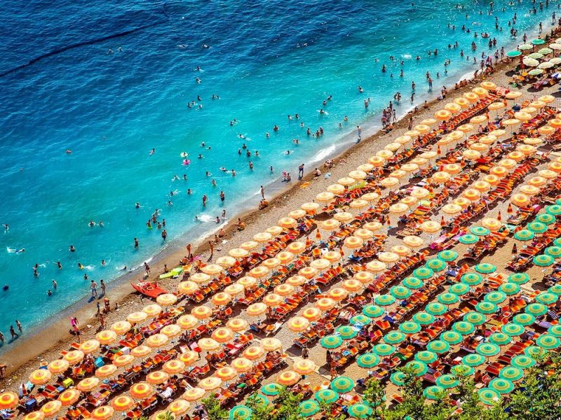 Aerial photography of tourists playing and taking sunbath on a sandy beach in Positano, Italy